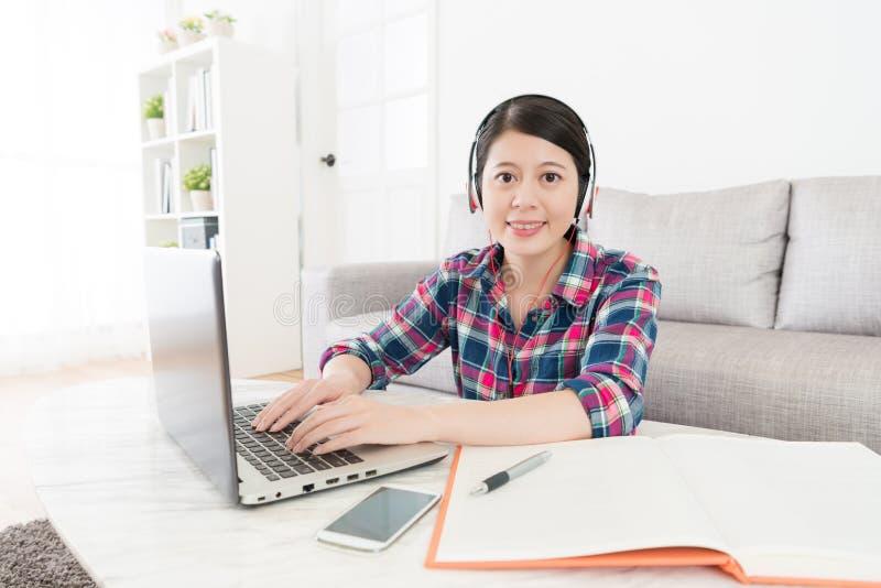 Sorriso auriculares vestindo do estudante consideravelmente fêmea fotos de stock