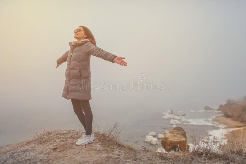 Sorriso bonito com os braços estendido no inverno da praia foto de stock royalty free