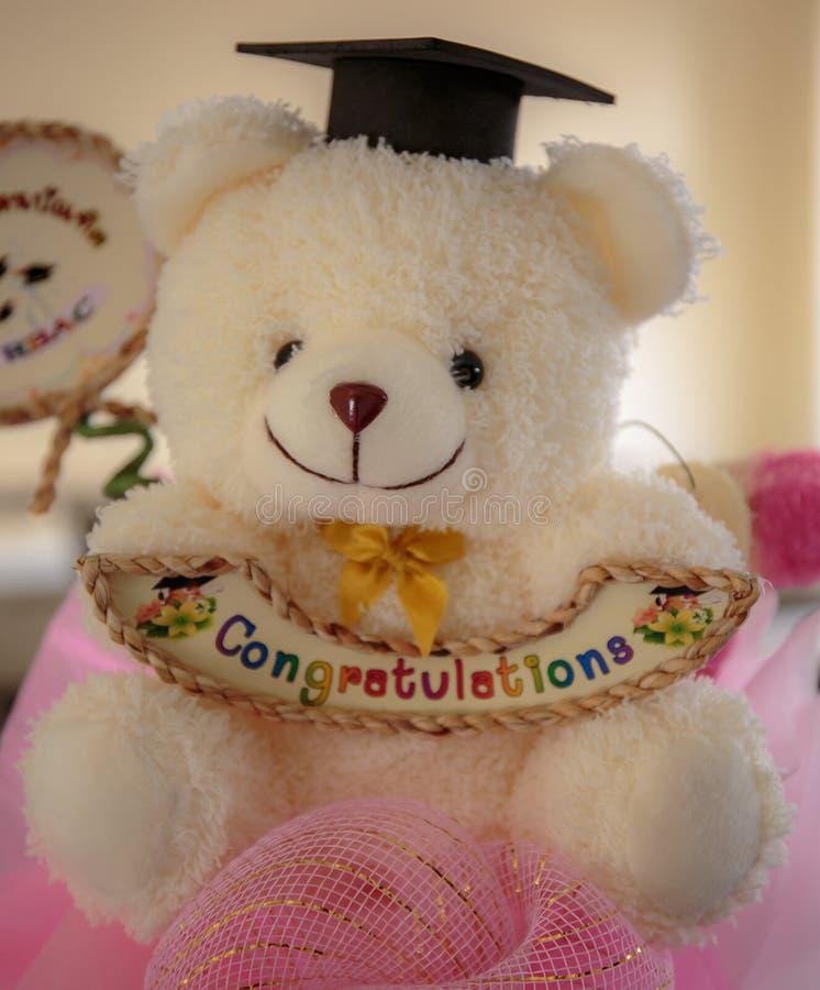 Sorriso bonito da boneca do urso branco com palavra das felicitações para o estudante imagens de stock royalty free