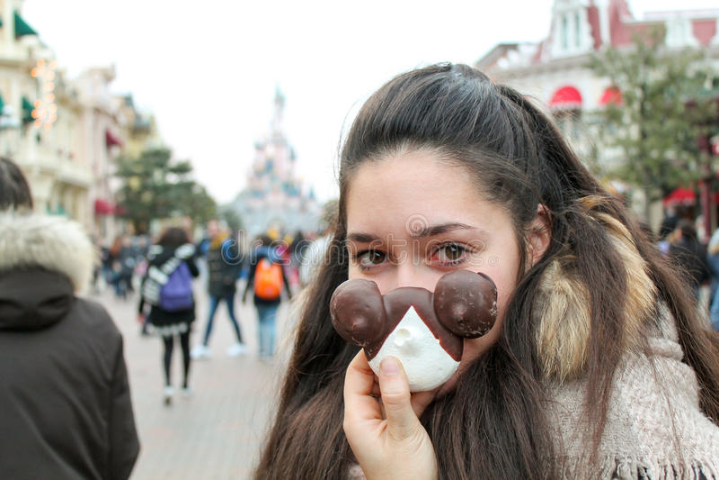 Sorriso bonito da menina com uma pastelaria na mão no funfair foto de stock royalty free