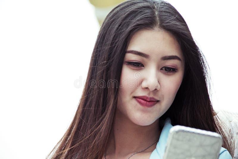 Sorriso bonito da mulher do close-up e vista do dispositivo do telefone celular imagens de stock