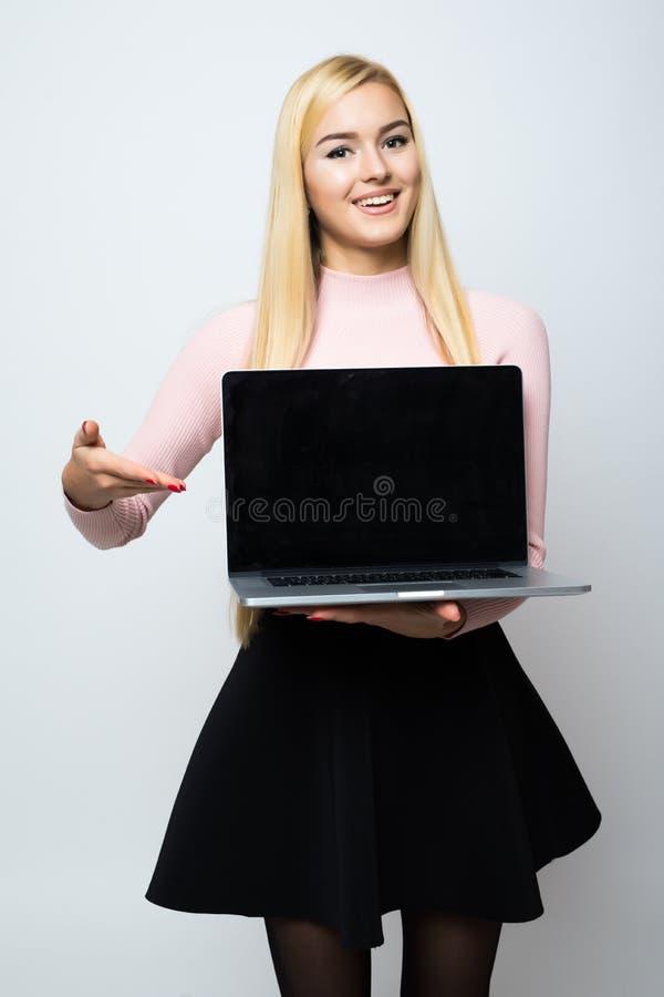 Sorriso bonito da mulher que olha a câmera, dedo do ponto na tela branca isolada do portátil sobre o fundo branco fotografia de stock royalty free