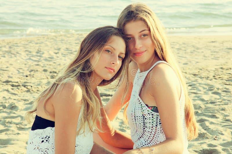 Sorriso bonito das meninas feliz na praia no estilo retro do por do sol fotografia de stock royalty free