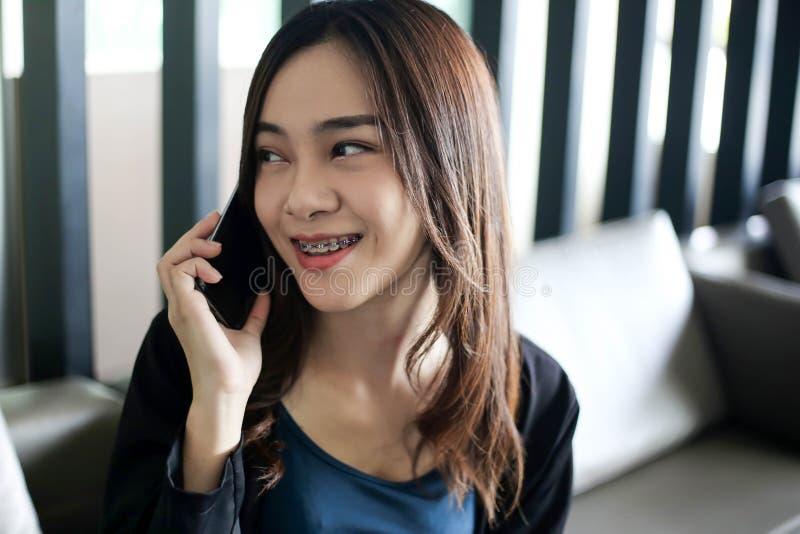 Sorriso bonito mulher de negócios felizmente asiática no revestimento do terno usando o telefone esperto, conceito do negócio fotografia de stock royalty free