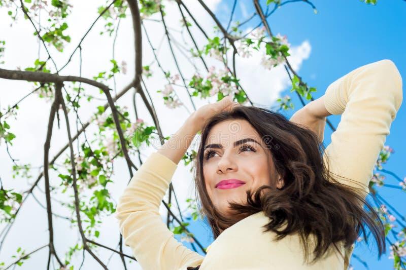 Sorriso bonito novo da mulher e parte traseira do céu azul sobre fotos de stock
