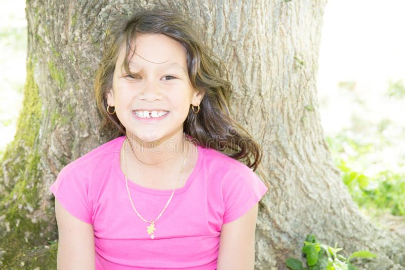 Sorriso bonito para o sul - a menina americana senta-se na árvore próxima verde imagens de stock royalty free
