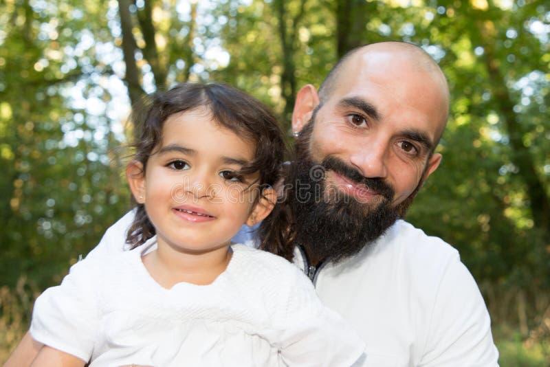 sorriso considerável do homem da barba calva com a filha da menina exterior no dia de verão fotos de stock royalty free