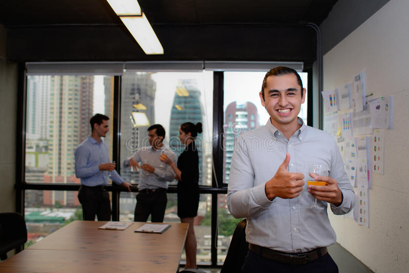Sorriso considerável do homem de negócios e polegares mostrar acima no escritório fotos de stock royalty free