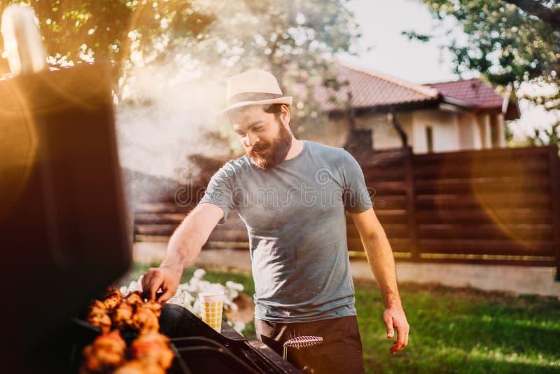 Sorriso considerável, grade de preparação masculina feliz do assado com carne e vegetais para amigos imagem de stock royalty free