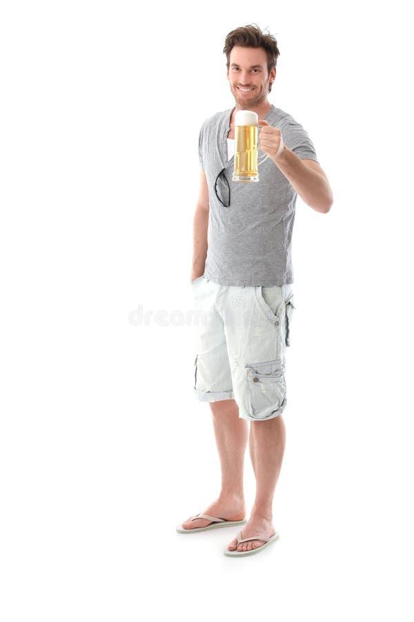 Sorriso da caneca de cerveja da terra arrendada do homem novo fotografia de stock