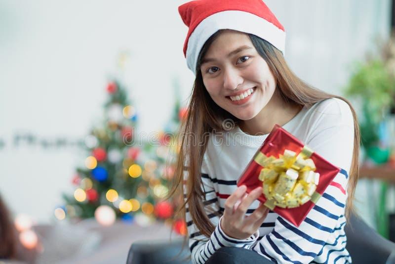 Sorriso da mulher de Ásia que guarda a caixa de presente do xmas do ouro na sagacidade da festa natalícia imagens de stock