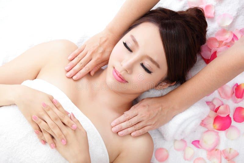 Sorriso da mulher que obtém a massagem no ombro foto de stock royalty free