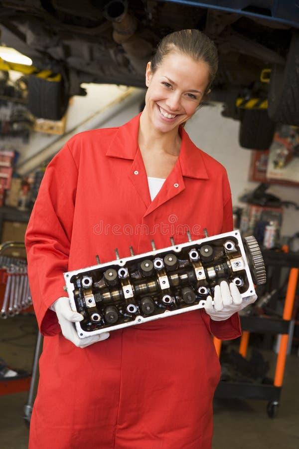 Sorriso da peça do carro da terra arrendada do mecânico fotografia de stock