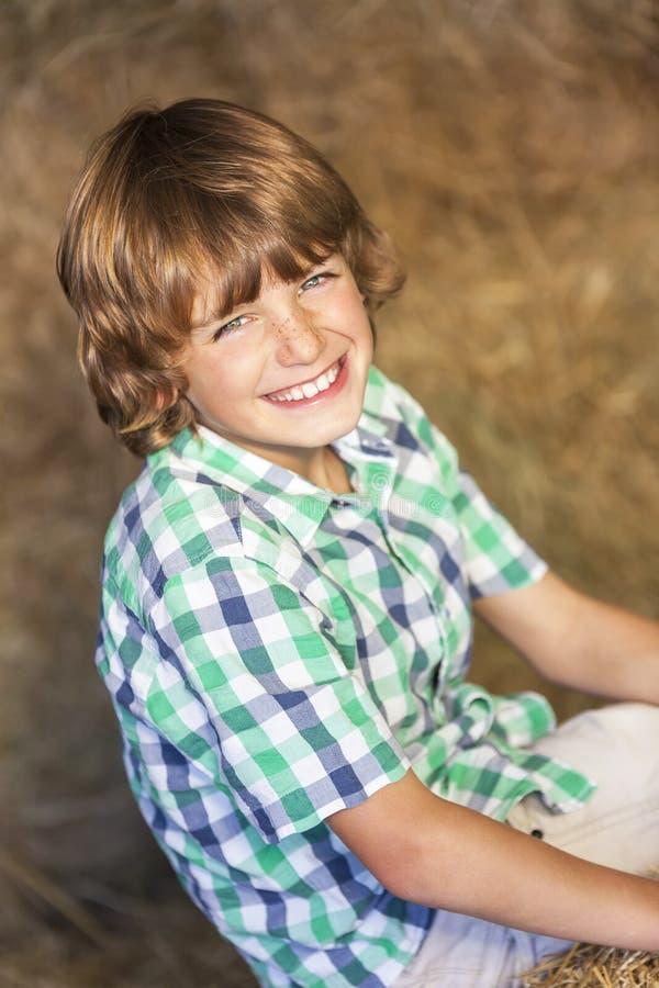 Sorriso de assento da criança feliz do menino em Hay Bales imagens de stock