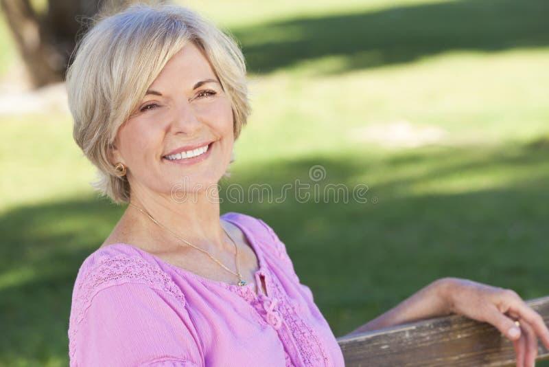 Sorriso de assento da parte externa da mulher sênior feliz fotos de stock