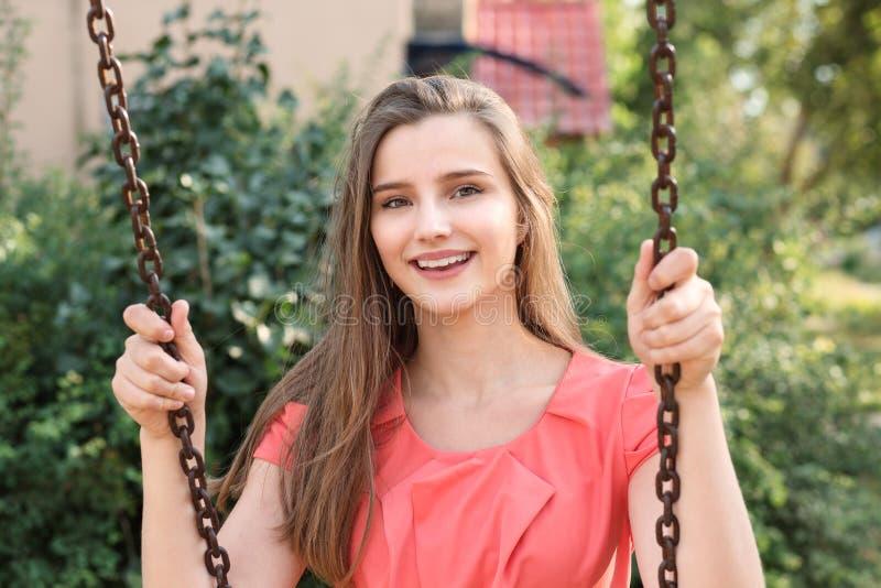 Sorriso de balanço da morena feliz bonita perto da casa no parque em um dia ensolarado imagens de stock royalty free