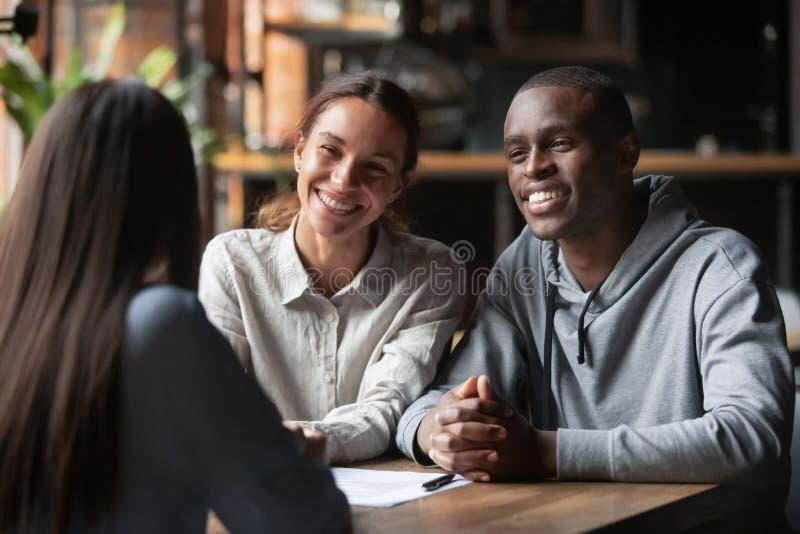 Sorriso de casal diverso ouvindo assessor financeiro ou corretor de imóveis foto de stock