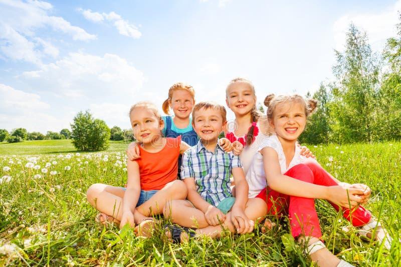Sorriso de cinco crianças que senta-se em uma grama imagens de stock royalty free