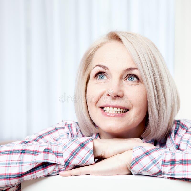 Sorriso de meia idade bonito ativo da mulher amigável e vista acima em casa na sala de visitas fim da face da mulher acima fotos de stock