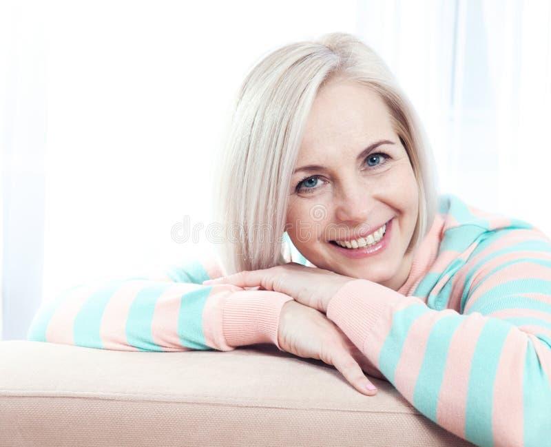 Sorriso de meia idade bonito ativo da mulher amigável e vista na câmera imagem de stock