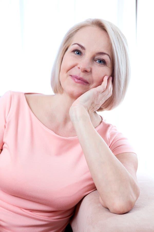 Sorriso de meia idade bonito ativo da mulher amigável e vista na câmera fim da face da mulher acima imagens de stock royalty free