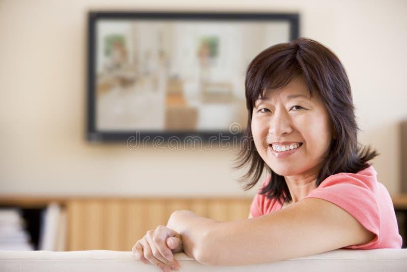 Sorriso de observação da televisão da mulher fotografia de stock royalty free