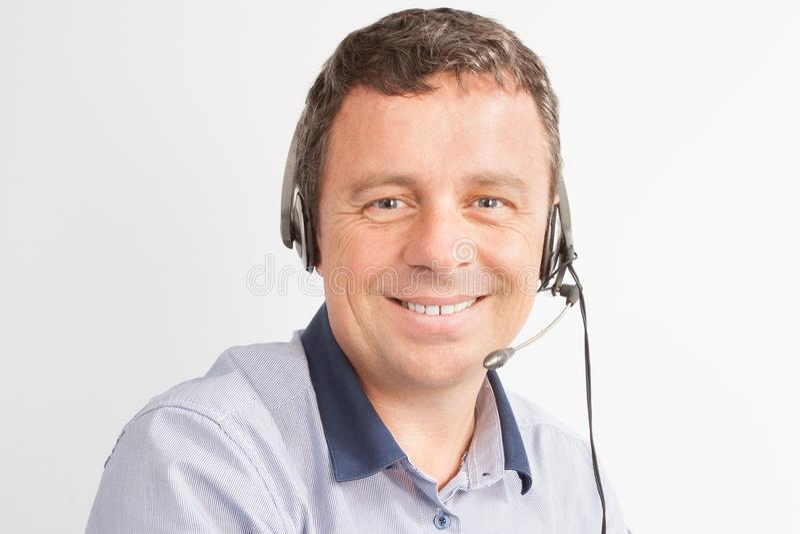 sorriso de trabalho do homem com os auriculares no centro de atendimento fotos de stock royalty free
