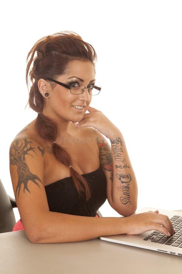 Sorriso del lato del computer dei tatuaggi della donna fotografia stock libera da diritti