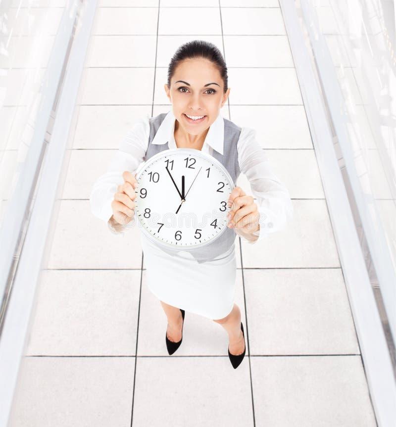 Sorriso della donna di affari, orologio della tenuta immagini stock