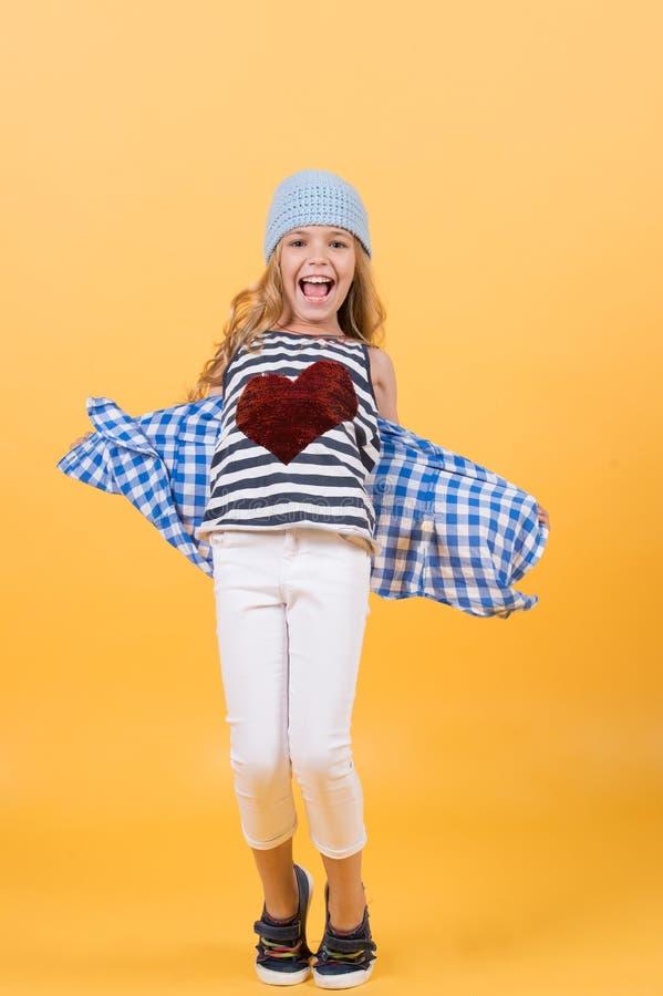 Sorriso della ragazza con cuore rosso sulla camicia su fondo arancio fotografia stock