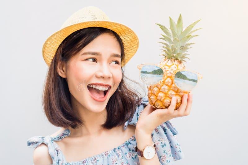 Sorriso della ragazza e allegro felici in vestito ed ananas blu della tenuta a disposizione fotografia stock libera da diritti