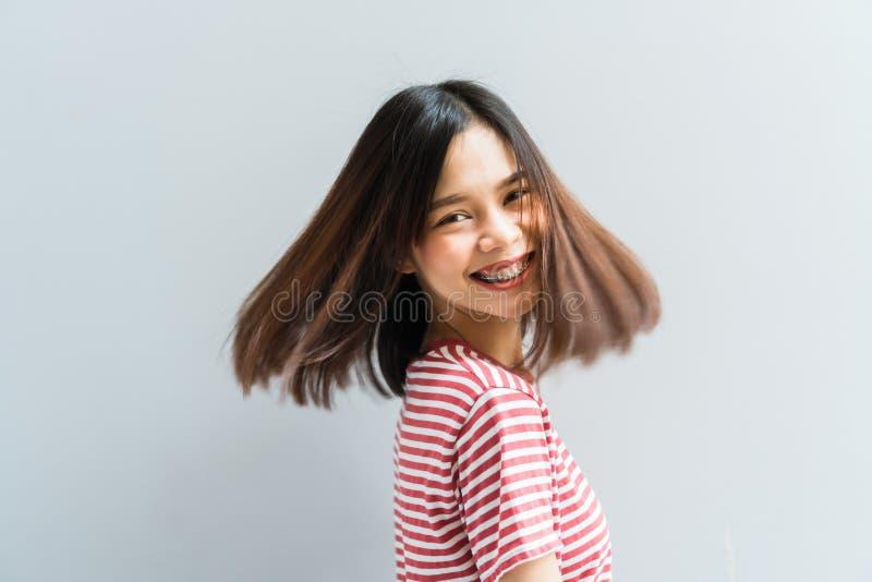 Sorriso della ragazza e allegro felici in vestito rosso in un gesto e nei capelli di turbine che fluttuano lungo la forza girante immagini stock