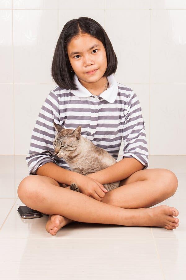 Sorriso della ragazza e soddisfatto svegli del gatto fotografie stock libere da diritti