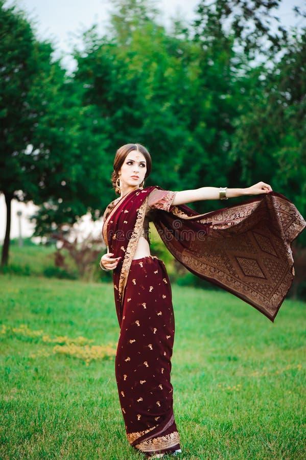Sorriso do retrato da menina indiana bonita Modelo indiano novo da mulher com grupo vermelho da joia imagem de stock royalty free
