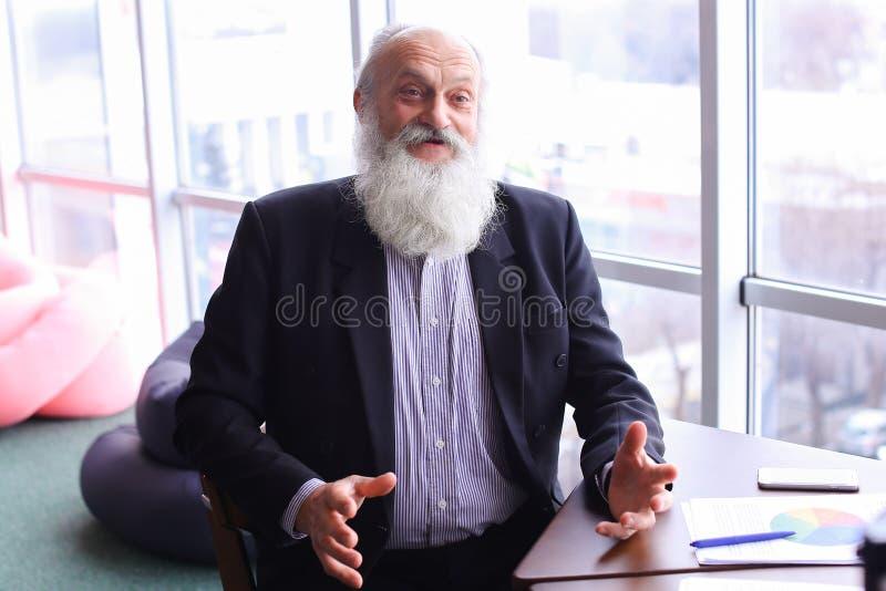 Sorriso e conversa do retrato do homem do diretor do veterano à câmera com em foto de stock