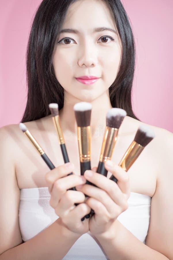 Sorriso e divertimento asiatici della donna dei capelli lunghi il giovani bei, toccano il suo fronte e tengono il set di pennelli immagini stock libere da diritti