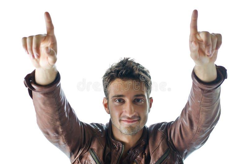 Sorriso e homem novo seguro que apontam os dedos acima fotos de stock royalty free