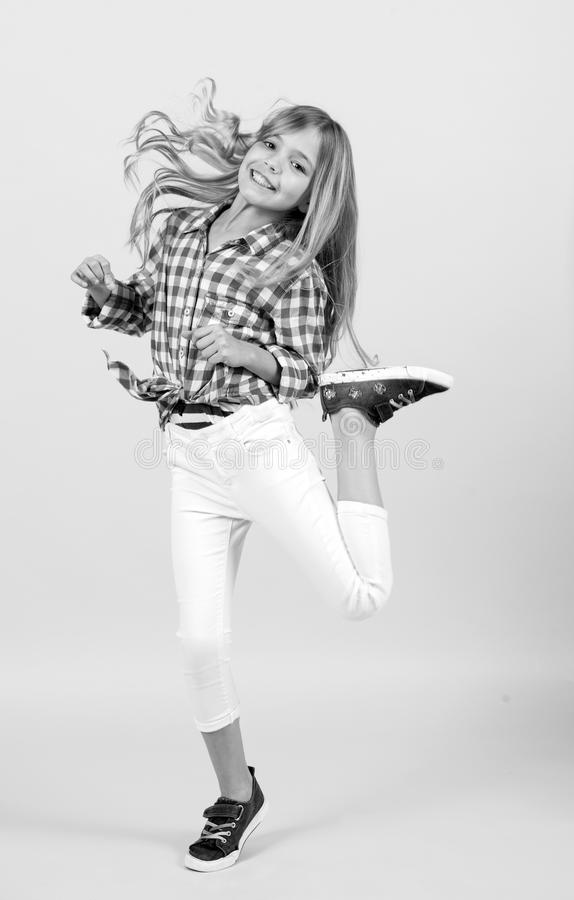 Sorriso e salto da criança da menina com cabelo longo louro foto de stock royalty free