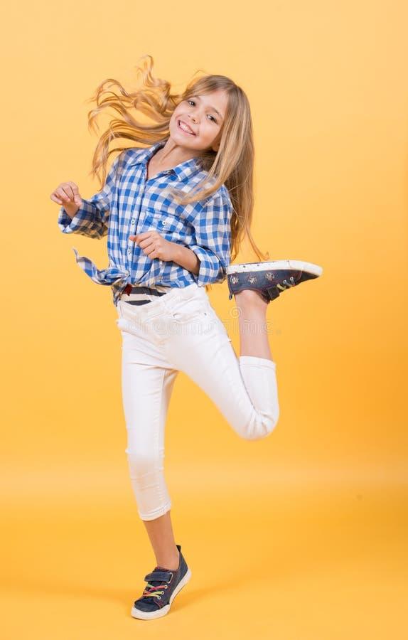 Sorriso e salto del bambino della ragazza con capelli lunghi biondi immagine stock libera da diritti