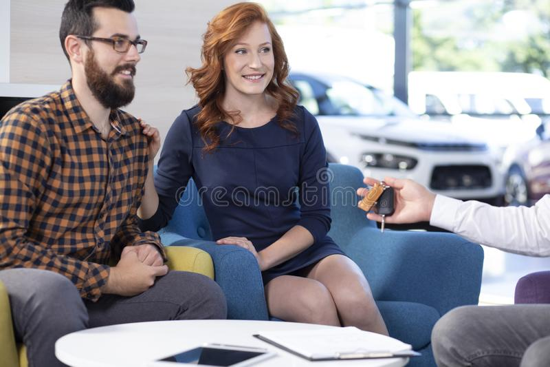 Sorriso e união feliz que compram um carro novo no showroo exclusivo fotos de stock