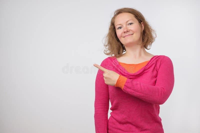 Sorriso europeu do swith da mulher que mostra o produto Menina bonita com cabelo encaracolado que aponta ao lado imagens de stock royalty free