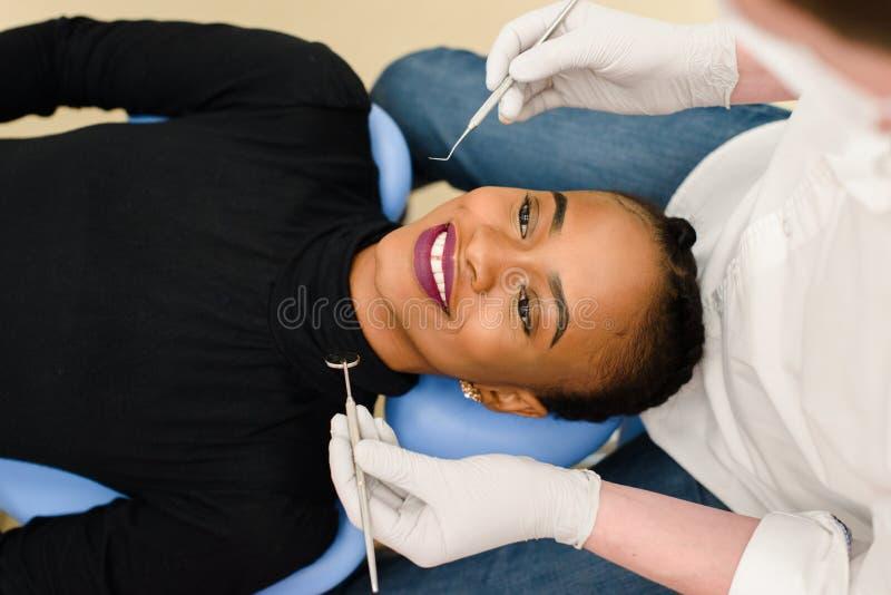 Sorriso fêmea preto étnico afro-americano novo quando dentista em condições de verificação brancas das luvas do látex de seus den imagens de stock royalty free
