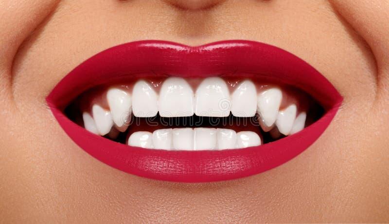 Sorriso felice con i denti bianchi sani, trucco rosso luminoso del primo piano delle labbra Cura di cosmetologia, di odontoiatria fotografia stock