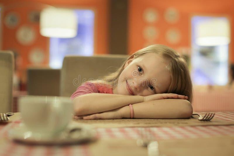 Sorriso felice del bambino alla macchina fotografica che mette la sua testa sulle sue mani al ristorante fotografia stock