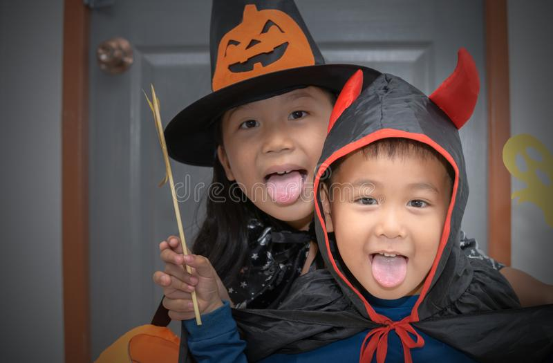 Sorriso felice del diavolo del ragazzo e piccola strega sveglia fotografia stock