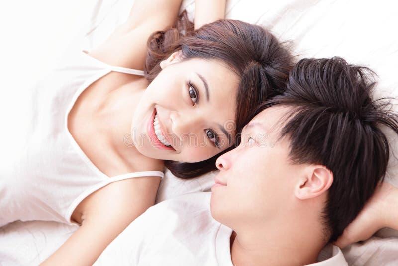 Sorriso felice delle coppie che guarda l'un l'altro a letto immagine stock libera da diritti