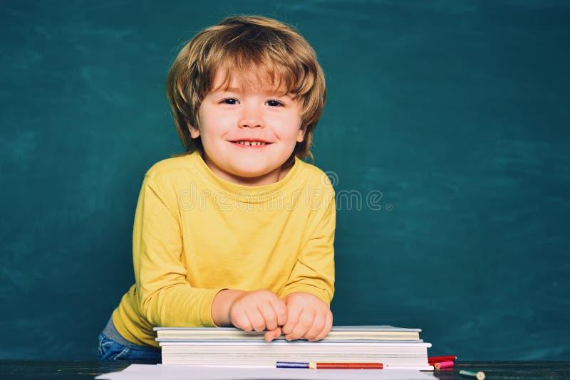 Sorriso feliz amplamente na escola Apronte para a escola Leitura da mam? com filho Educa??o home imagem de stock