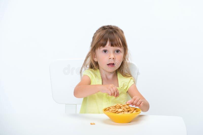 Sorriso feliz bonito criança de 3 anos emocional e positiva da menina no t-shirt amarelo que come flocos do cereal na tabela isol fotografia de stock