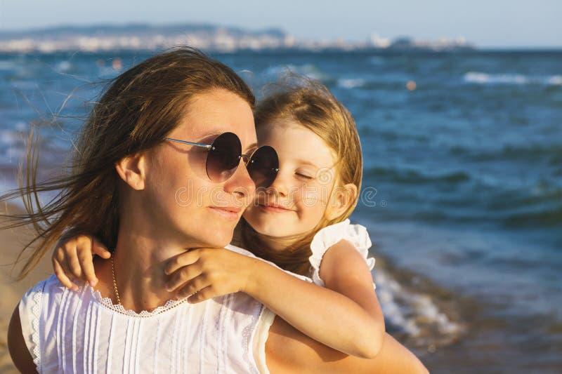 Sorriso feliz da mamã e da filha em se ao andar perto do mar em uma noite ensolarada morna fotografia de stock