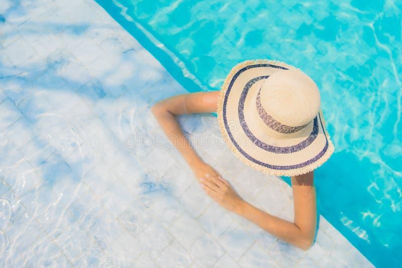 Sorriso feliz da mulher asiática nova bonita do retrato para relaxar na piscina para férias do curso fotos de stock royalty free